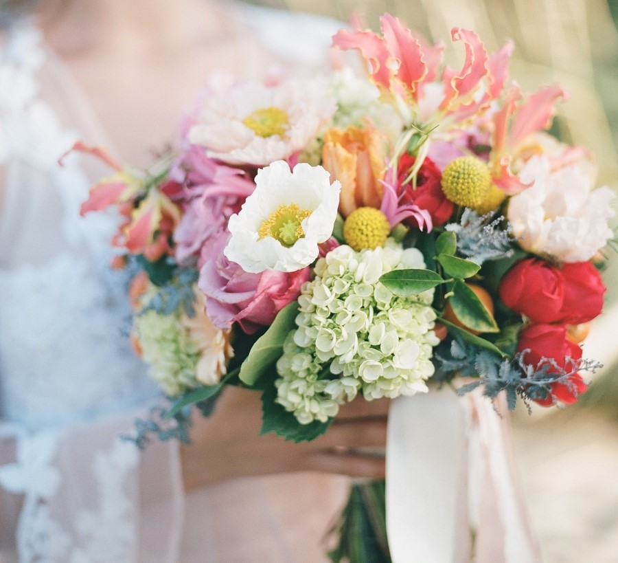 Lush bridal bouquet of spring flowers, white poppy, orange parot tulips, red garden roses, gorgeous gloriosa, green hydrangea, pink nerine lily, yellow craspedia, pink roses, and kumquats