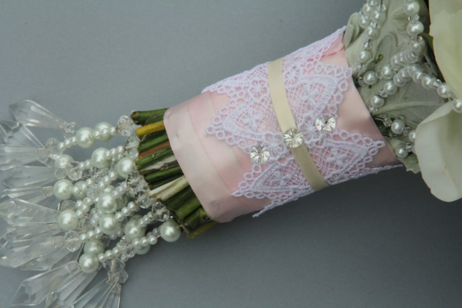 Wedding bouquet wrapping  with  a lace, ribbon and crystal pins. A hand made beaded frame for the bouquet